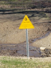 The sign says caution Rattesnakes. They are about in the summer during the night or hiding under rocks to keep cool.