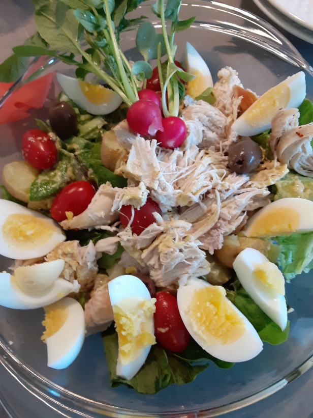 chicken and eggs on fresh greens, radishes, olives and potatoes